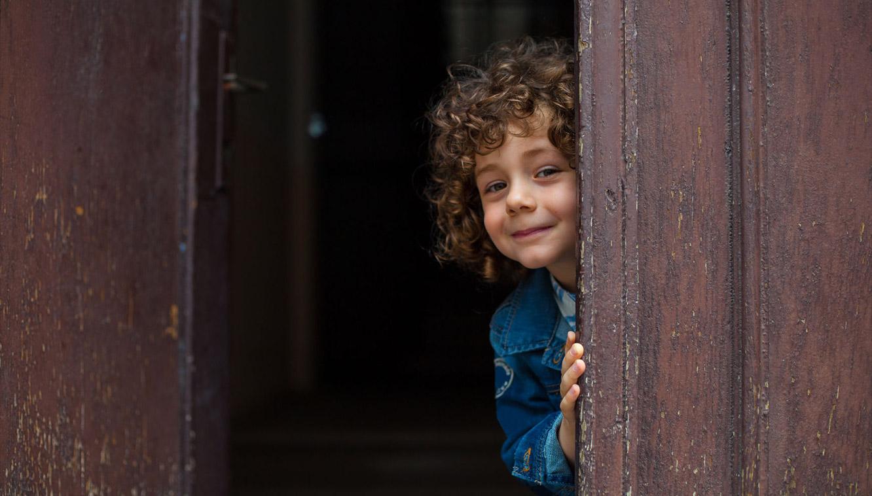 Happy Child Peering around a Corner